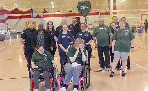 Men and women in TPS uniform with a group of adults and children in green T-shirts in a gym