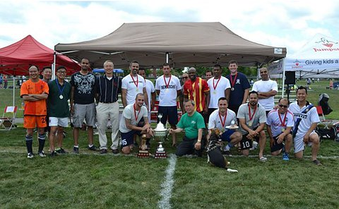 A group of men in soccer uniform, several holding a trophy