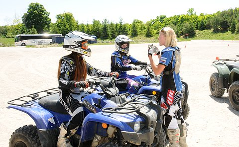 A woman talks to two girls on ATVs wearing safety equipment