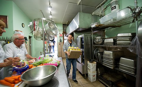 A man carries canned food through kitchen as a man cuts vegetables