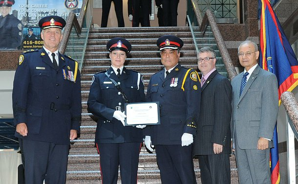 Two men in TPS uniform, one women in TPS uniform standing with two other men on a staircase