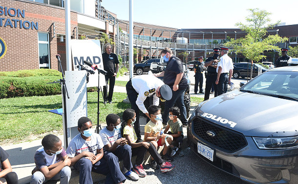 A man in a police uniform is leaning over to put a mask on a young boy. A group of youth is sitting on the curb next to a police vehicle, while a group of adults are standing behind them.