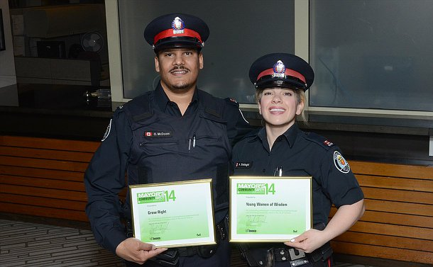A man and woman in TPS uniforms holding framed certificates