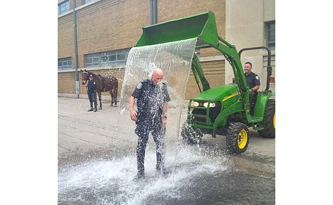 A man in TPS uniform is drenched in water from a front loader tractor driven by a man in TPS uniform