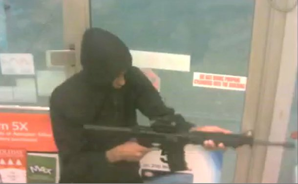 A person in a hood holding an assault rifle
