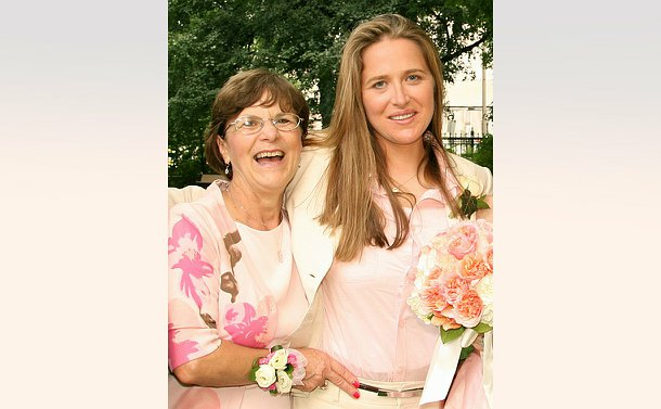 A woman with her mother both are wearing pink and appear to be at a wedding.