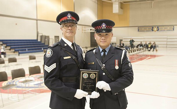 A man in TPS uniform and a man in Auxiliary uniform holding a plaque