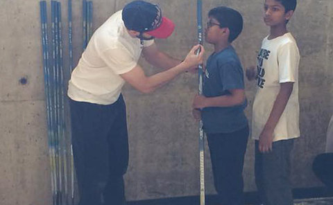A man holds a hockey stick to the chin of boy in a gym