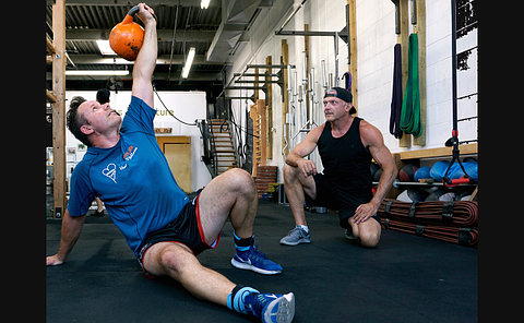 A man crouches beside another man lifting a kettle bell over his head