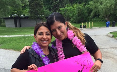 Two women holding pink sign with text: Girlz will be Girlz