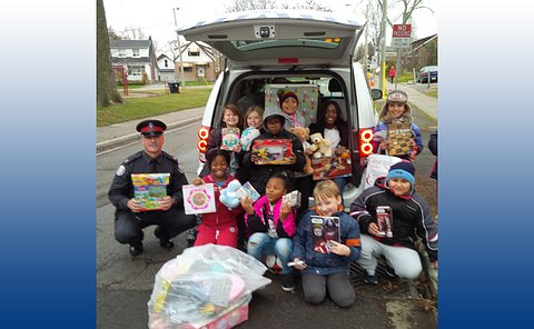 Boys and girls with a man in TPS uniform with toys beside a minivan