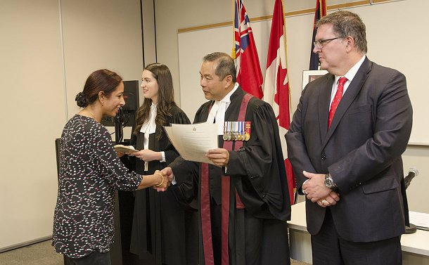 A woman is handed a certificate by a man in a black robe beside a woman and another man