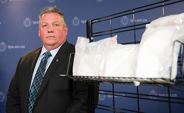 A man in a suit next to a display of drugs in clear plastic bags.