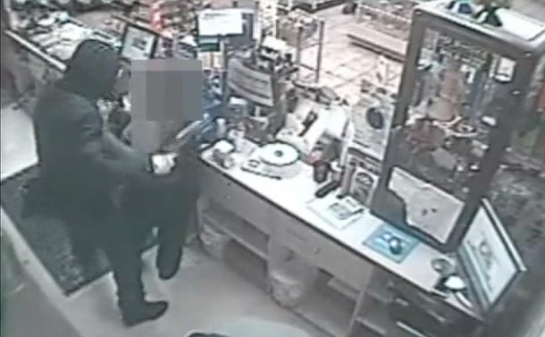 A hooded man holding a gun behind a counter with a  woman with her face pixelated from view