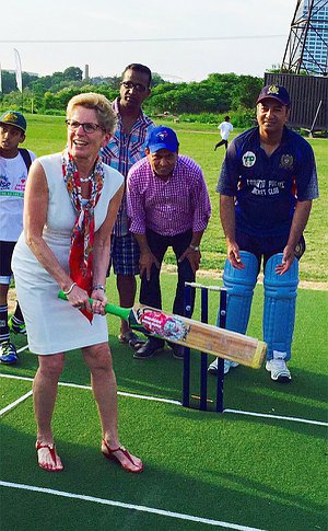 A woman stands holding a cricket bat with others surrounding her
