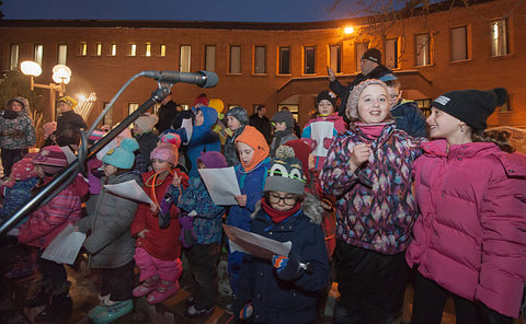 Children singing outside a building