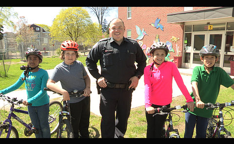 A man in TPS uniform with four children wearing helmets on bicycles