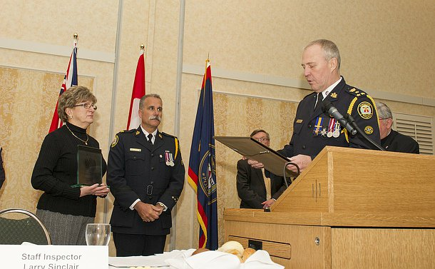 Two men in TPS uniform with a woman holding a glass award