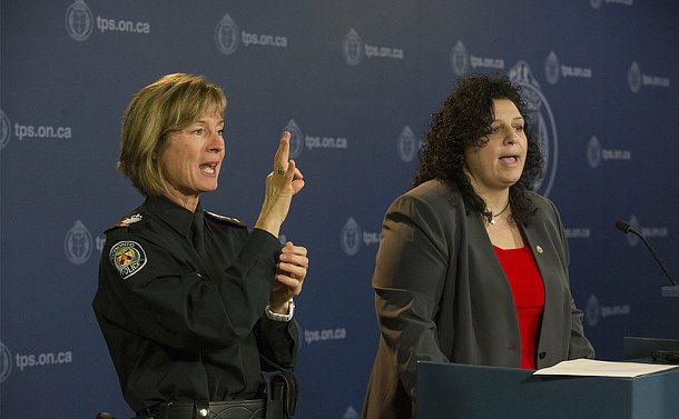 A woman in TPS uniform gesticulates with her hands as another woman speaks at a podium