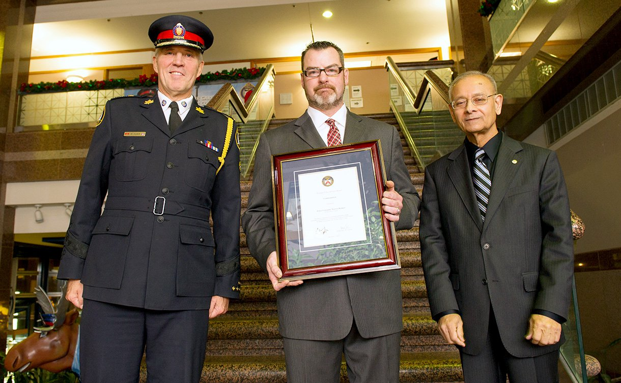 Three men, one wearing a TPS uniform, one holding a framed certificate and another standing. All standing in a row