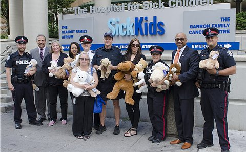 A group of people, some in TPS uniform, in front of a Sick Kids sign holding teddy bears
