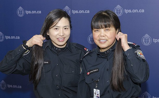 Two women in TPS uniform hold their hair in ponytails
