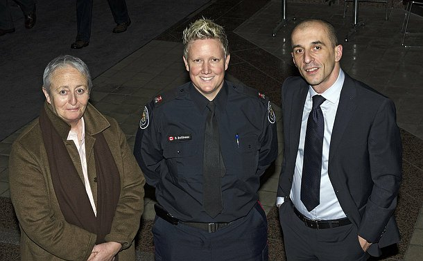 Two women (one in police uniform) and a man standing in the hallway of a building