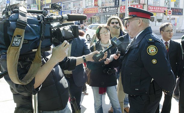 Man in a police uniform talks to television reporters