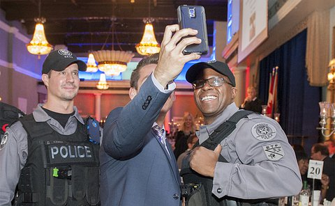 A man holds a cellphone up between two TPS officers