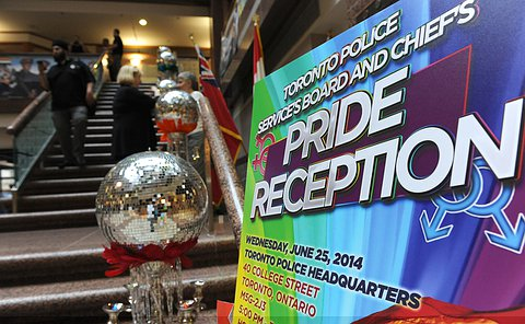 A Pride reception poster board beside a decorative fixture with a disco ball on it