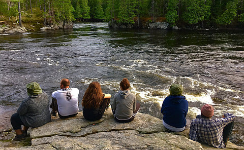 A group of people sit on a large rock facing a river