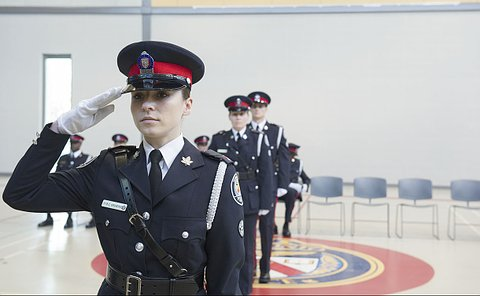 A woman in TPS uniform saluting