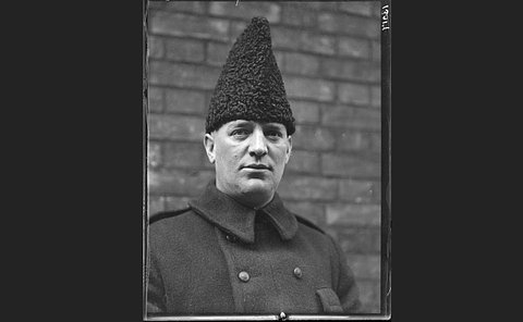 A man in a high woolen hat and overcoat