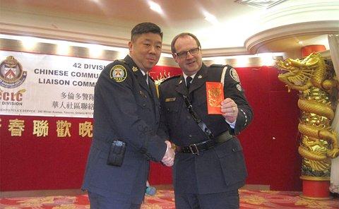 Two men in TPS uniform shake hands