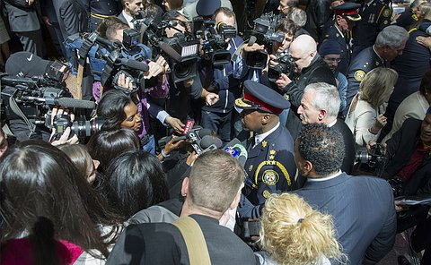 A group of reporters with video cameras around a  man in TPS uniform