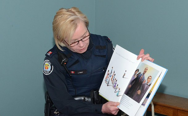 A woman in TPS uniform reads from a book opened toward her audience