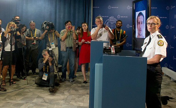 A woman at a podium beside a photo of a man on a TV with reporters with video and still cameras looking on