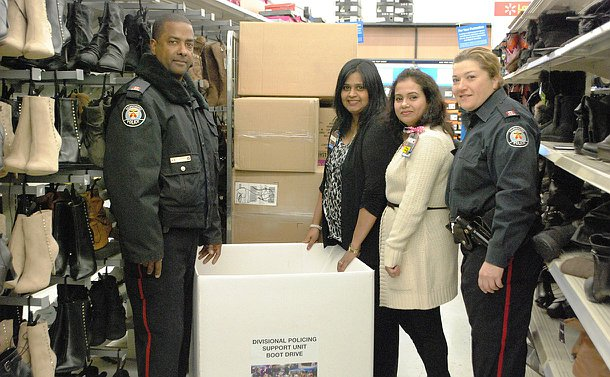 One man and one woman in Toronto Police uniform stand with two other women in front of a large donation box in the boot aisle of a retail store