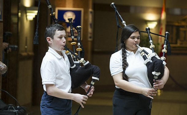 A boy and a girl playing bagpipes
