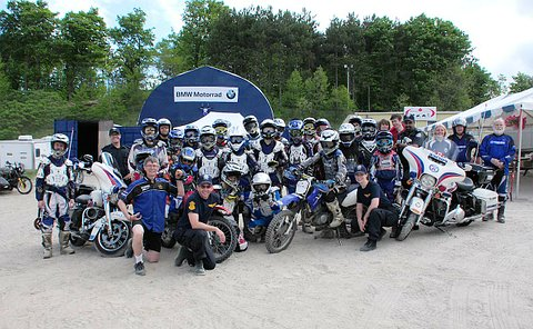 A large group of people in dirt bike protective gear with others