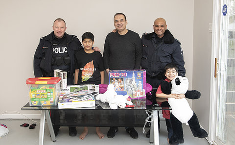 Two men in TPS uniform with two boys and a man with a table of toys