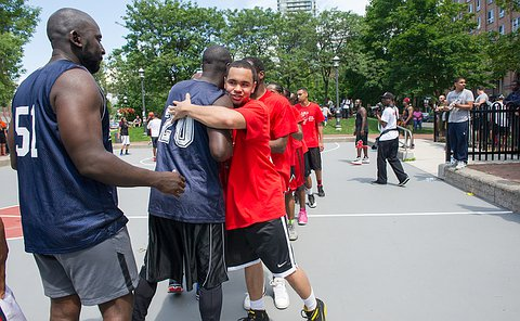 A line up of men in dark blue basketball uniforms with their backs to the camera, while the one in the middle is hugged by a young man in a red shirt who is facing the camera.