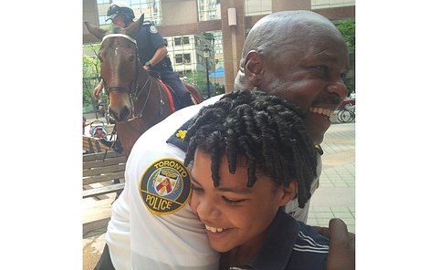 A man in TPS uniform hugs a boy with a man in TPS uniform on horseback behind them