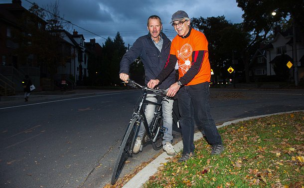 A man in an organe T-shirt is putting a light on a man's bike who is standing on his bike.