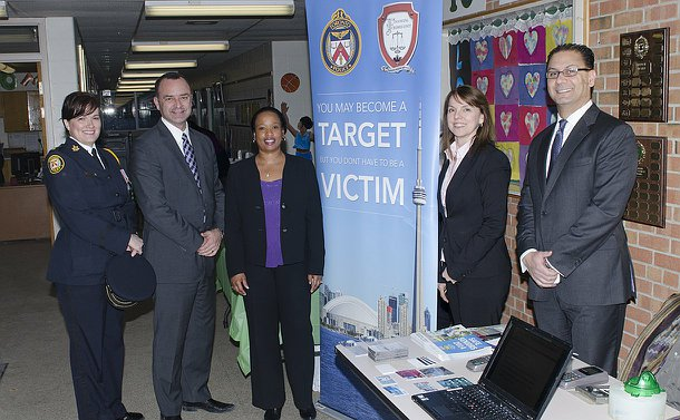 One woman in TPS uniform and four other in business wear stand in front of a fraud prevention display