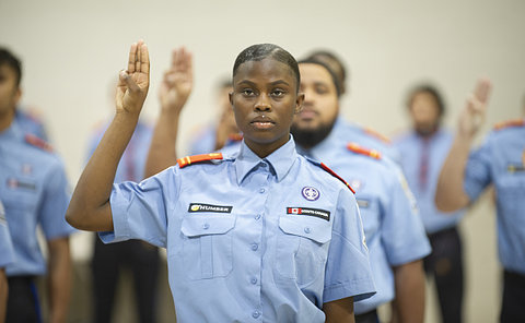 A woman in TPS rover uniform with her hand raised