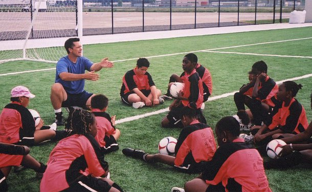 A man kneels and points forward and children in the same uniform sit around him on a soccer field