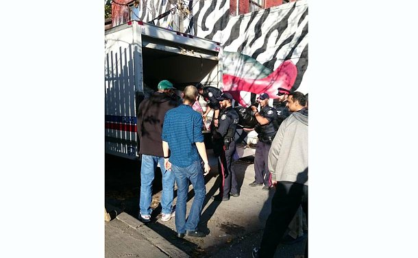 A group of people, some in TPS uniform unloading a cube truck