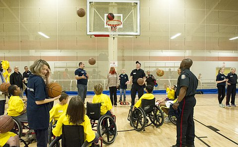Men in TPS uniform look up at a basketball net as children in wheelchairs throw basketballs in the air