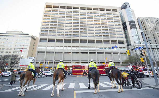 A line of officers on horses with other emergency vehicles